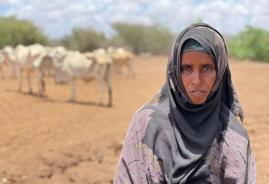 woman in purple headscarf standing on dry farmland