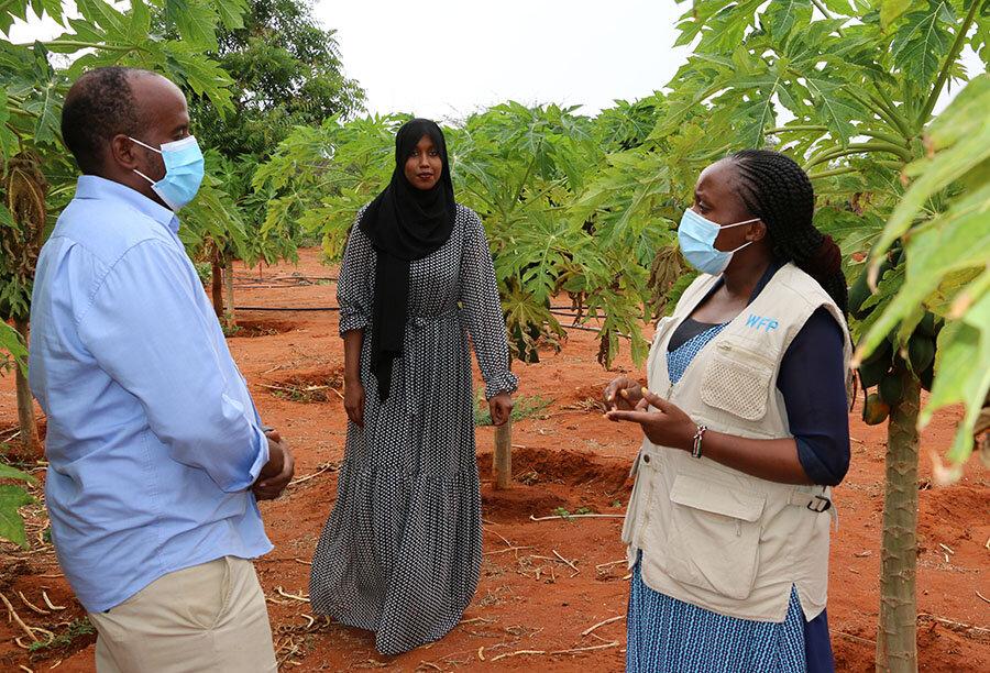woman and man in COVID health masks talk on farm