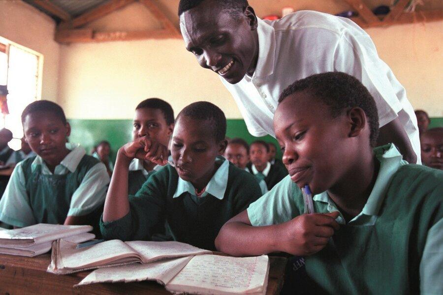 man speaks to schoolchildren in green uniforms