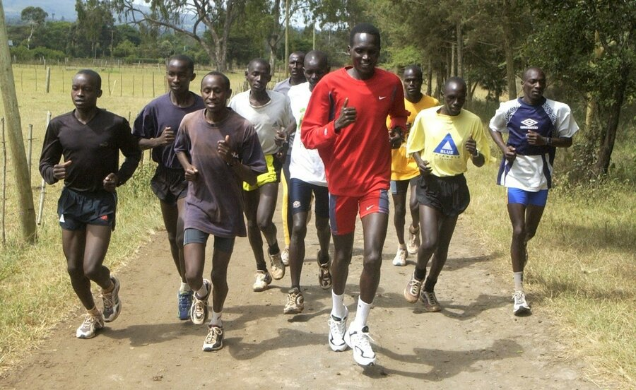 man in red shirt running with schoolchildren