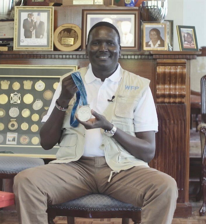 man in WFP vest posing with Olympic medals