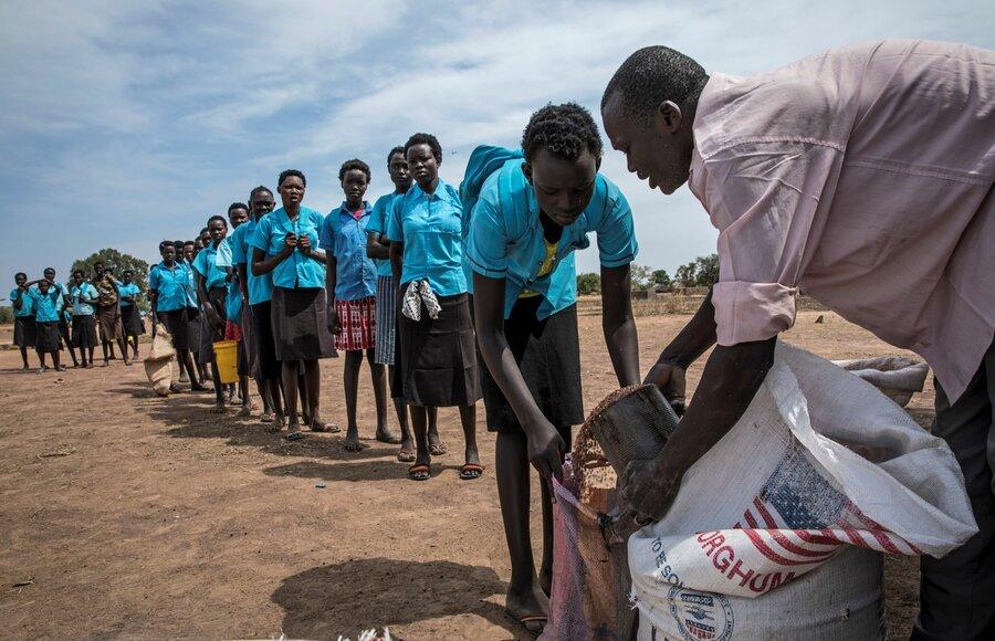 schoolchildren in blue uniforms line up for food