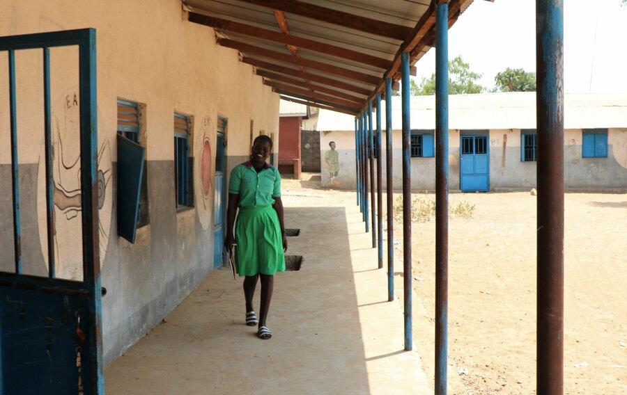 schoolgirl in green uniform smiling and walking