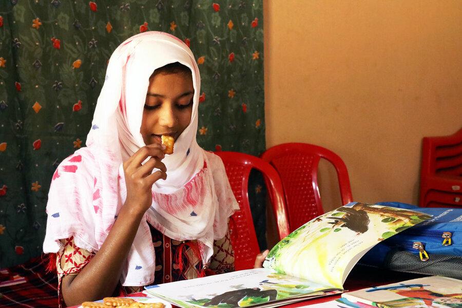 schoolgirl eating biscuit and reading