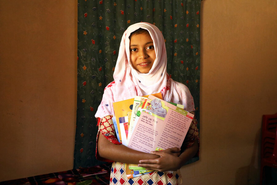 young schoolgirl in pink headscarf holding book