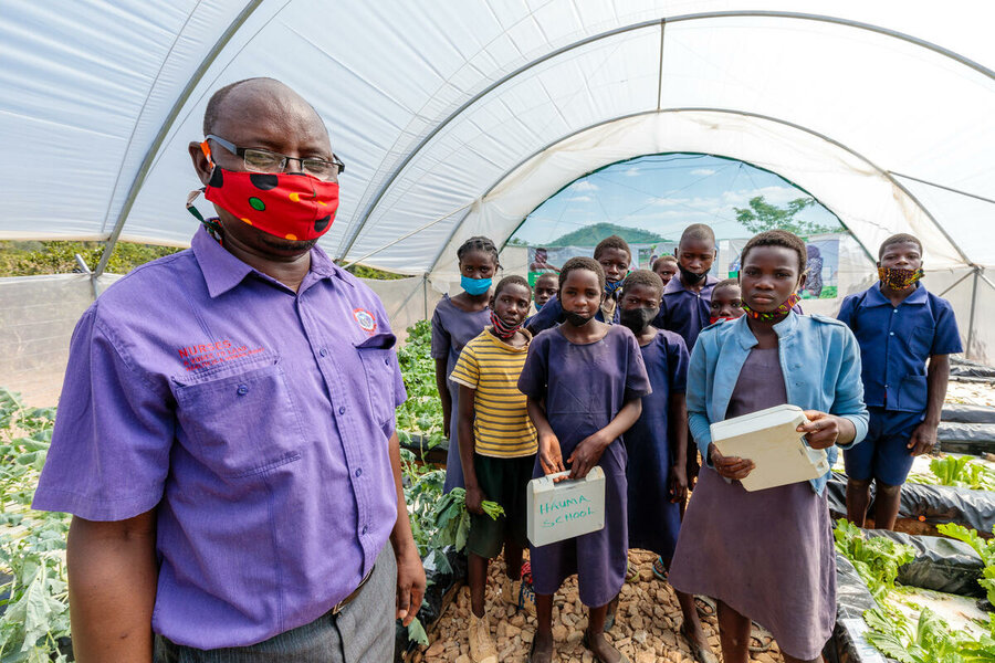 teacher in COVID face mask stands with students in greenhouse