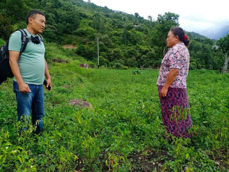 woman in purple shirt stands in field and talks to man