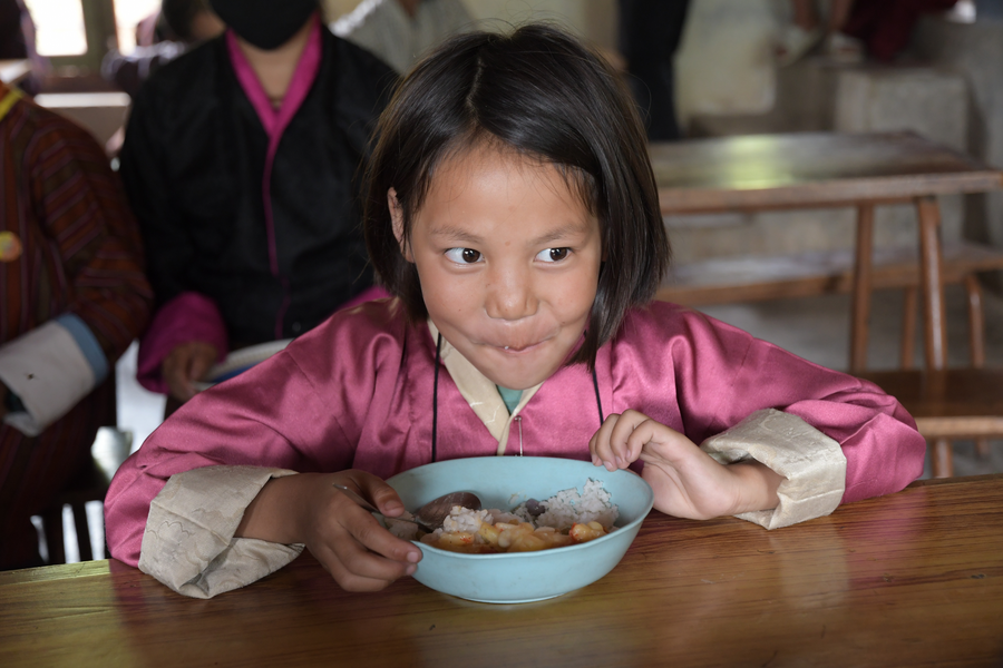 little girl in pink shirt eats food and smiles