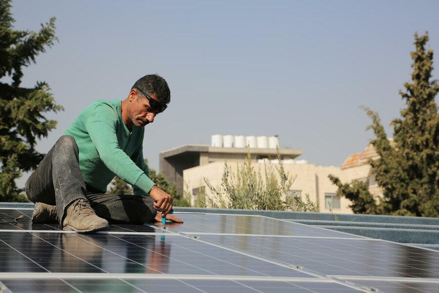man installing solar panel on roof