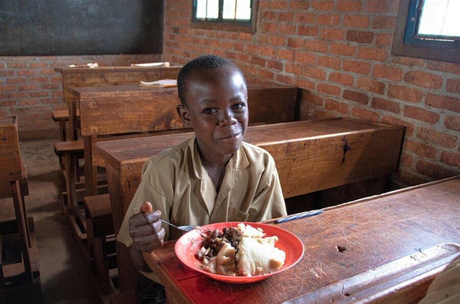 boy in brown school uniform eating lunch
