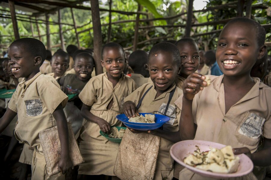 schoolchildren in brown uniforms eating