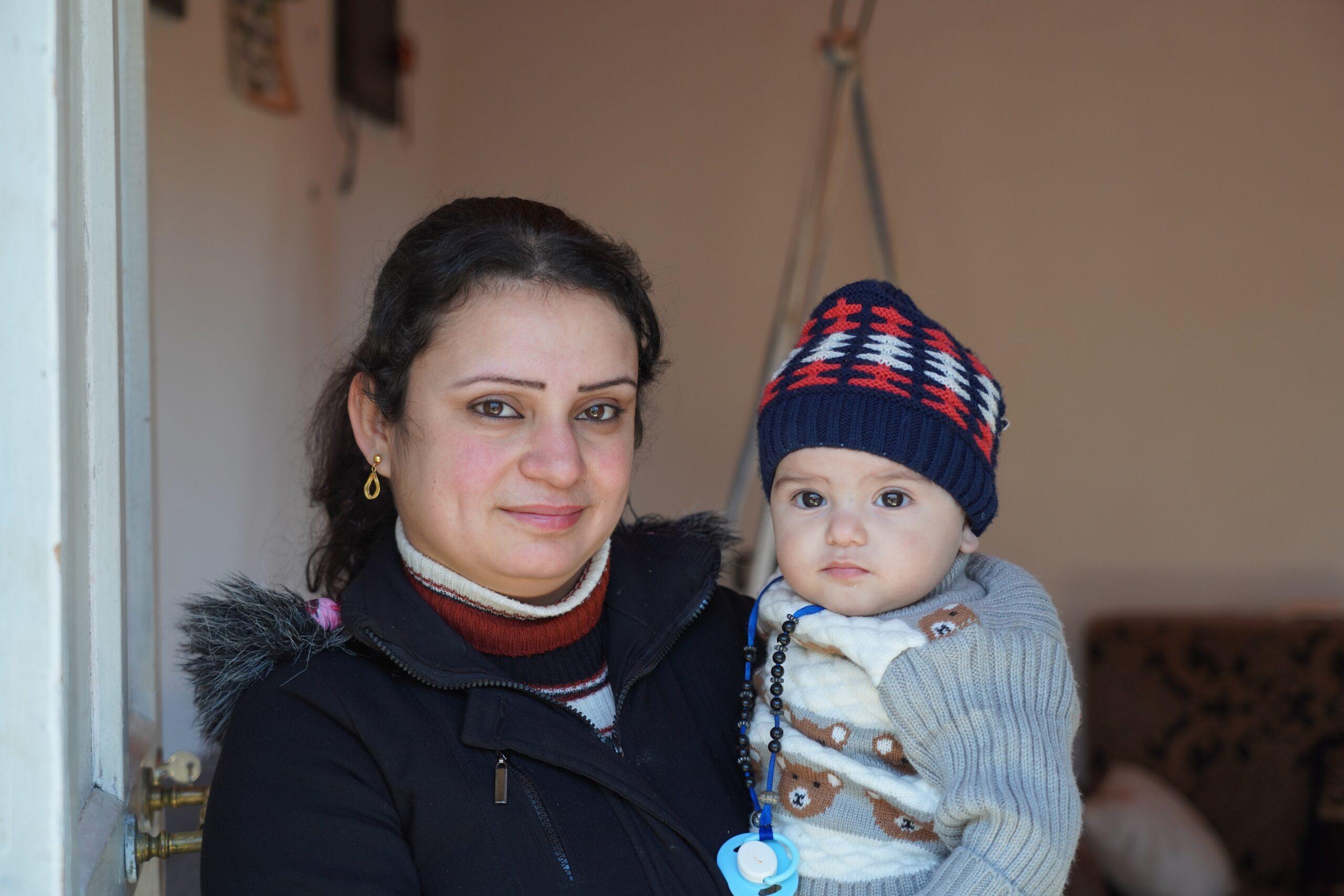 woman smiling holding little boy in winter hat