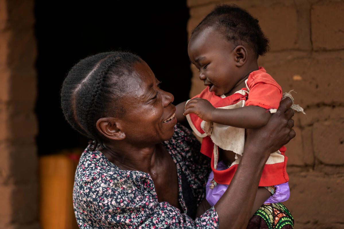 woman holding her grandson and smiling
