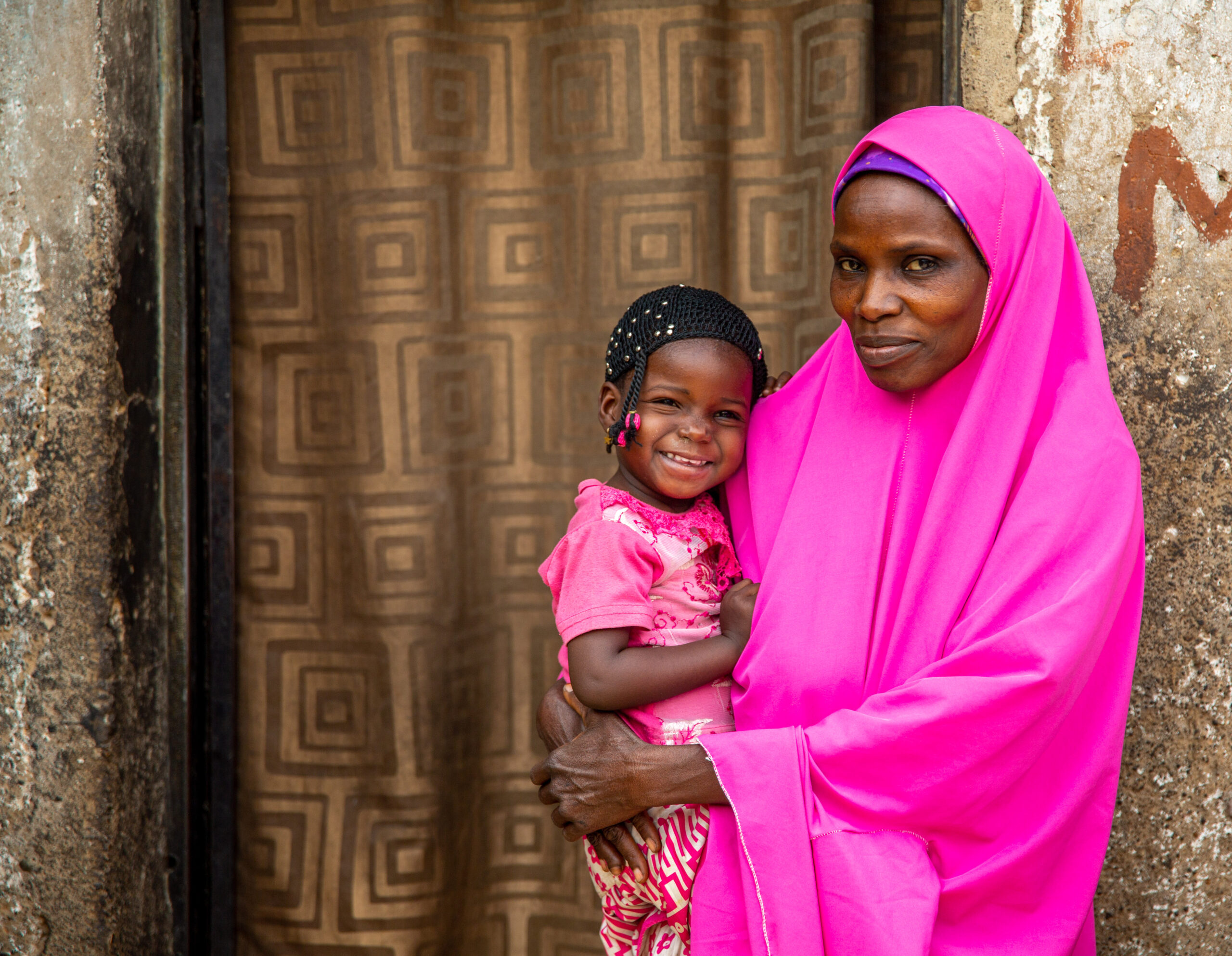 woman in full pink headscarf holding little girl