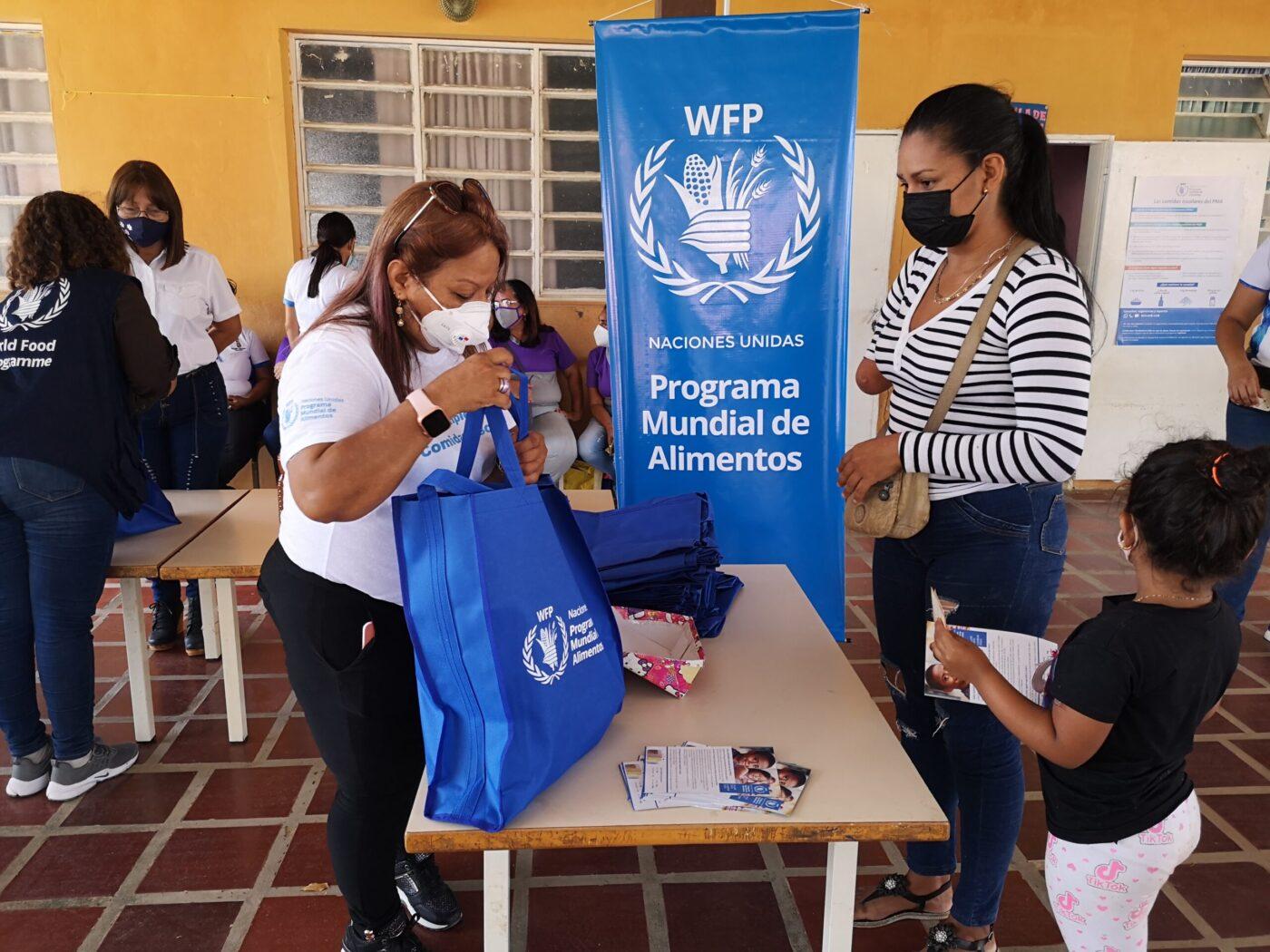 women in health masks exchanging bag of food