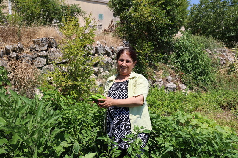 woman stands in garden holding vegetable and smiling