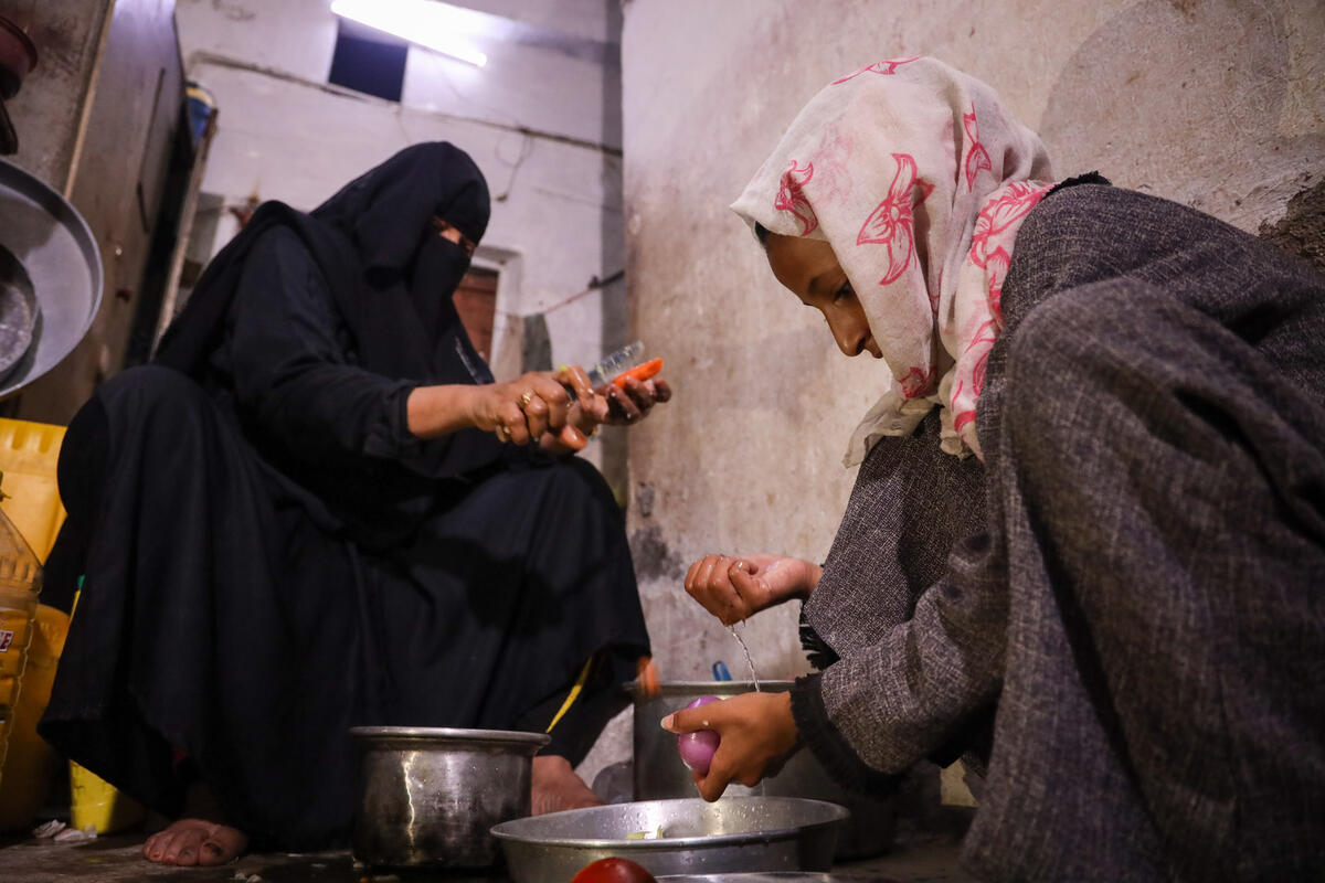 woman in full black burqa cooking in kitchen with granddaughter