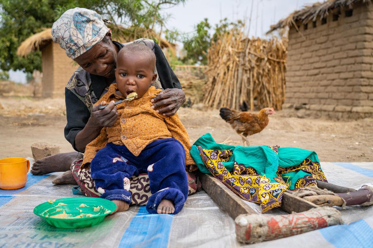 grandmother feeds little boy porridge