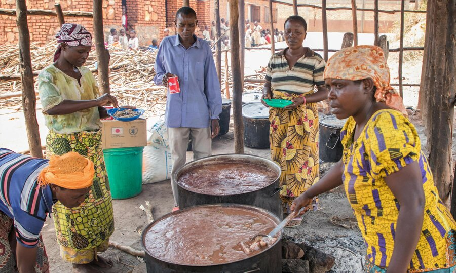 men and women cooking around large pots