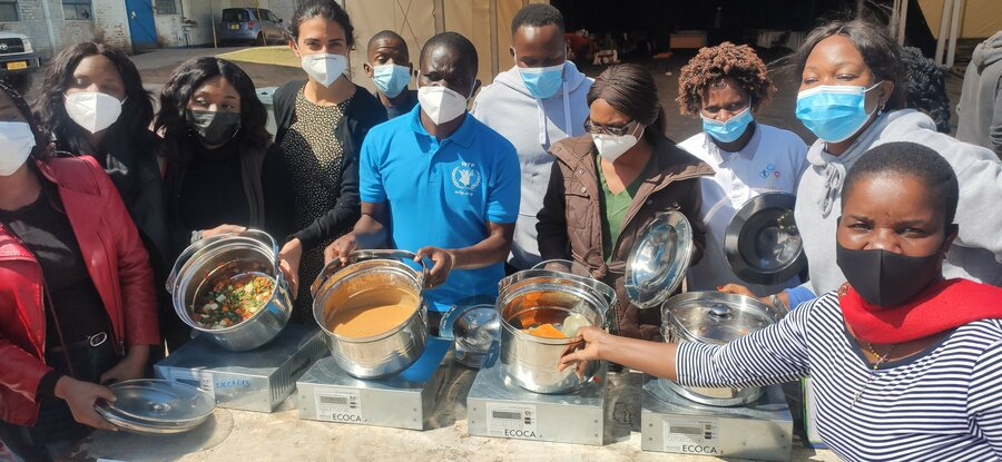 group of people standing with cooking ware in COVID masks