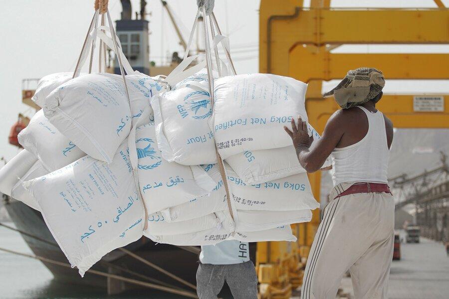 man lifting bags of food