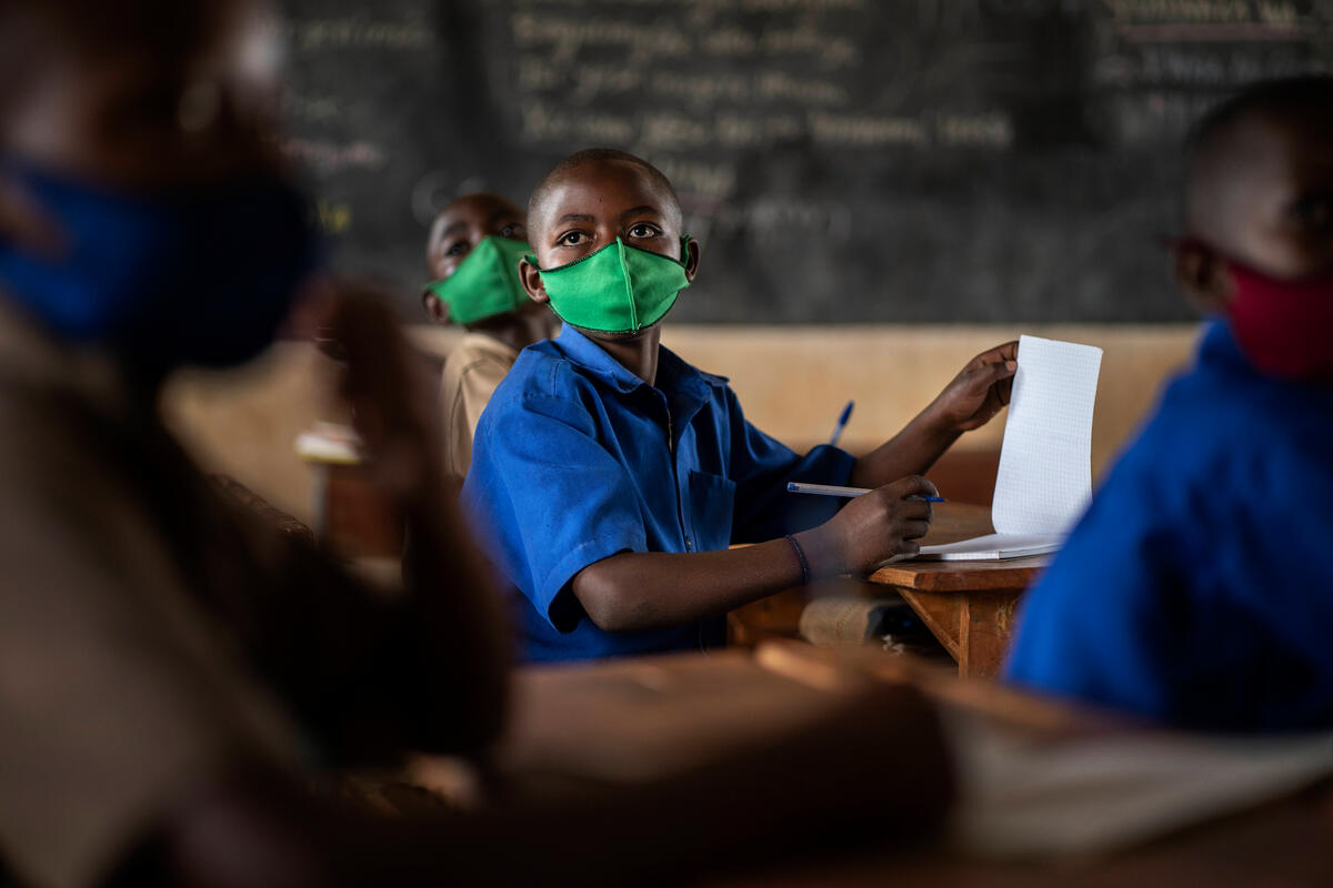 boy in blue uniform and green COVID health mask in classroom