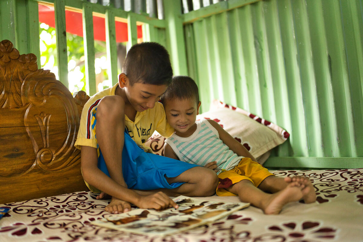 two boys smiling and reading on a bed