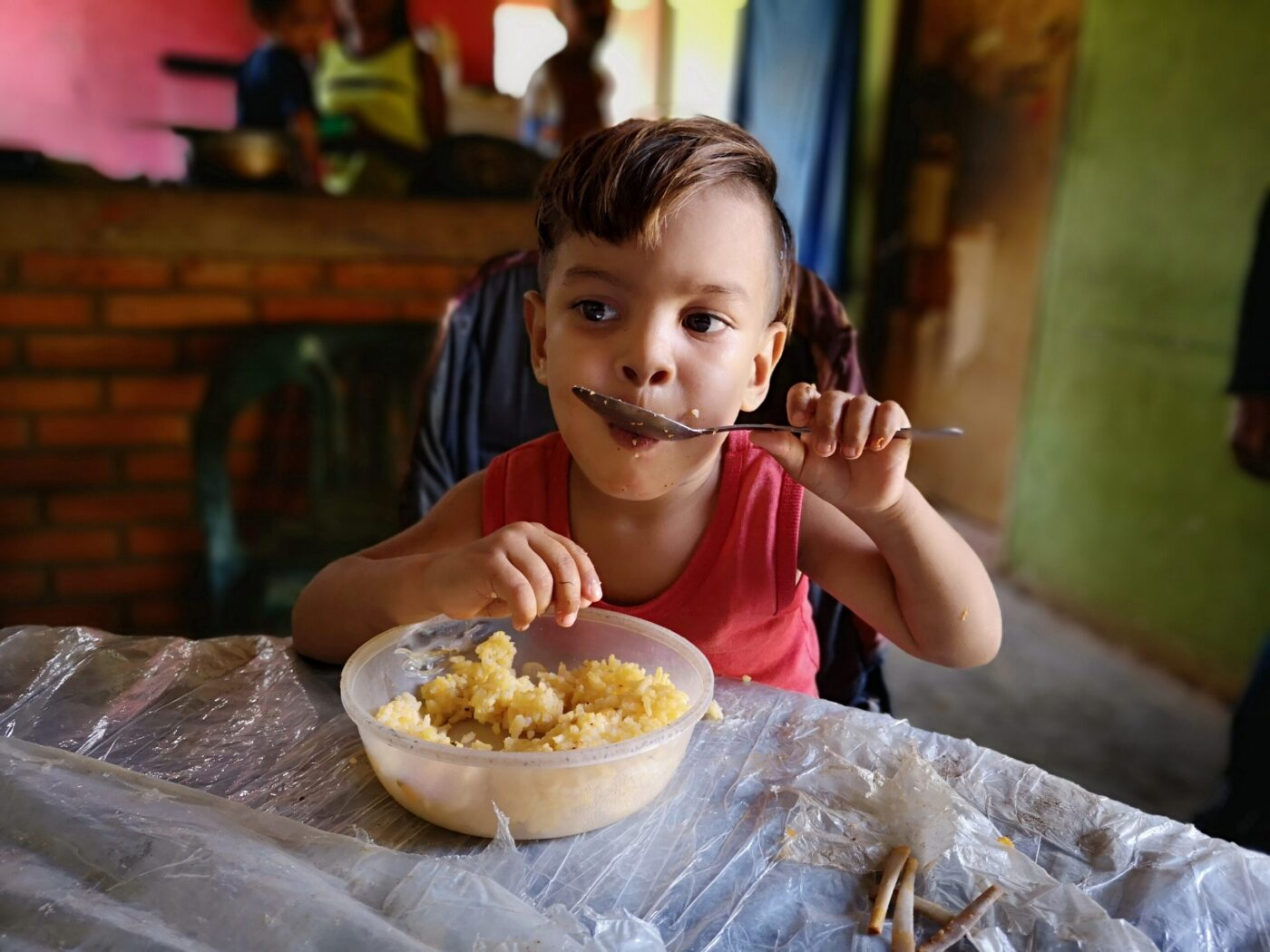 little boy eating food at table