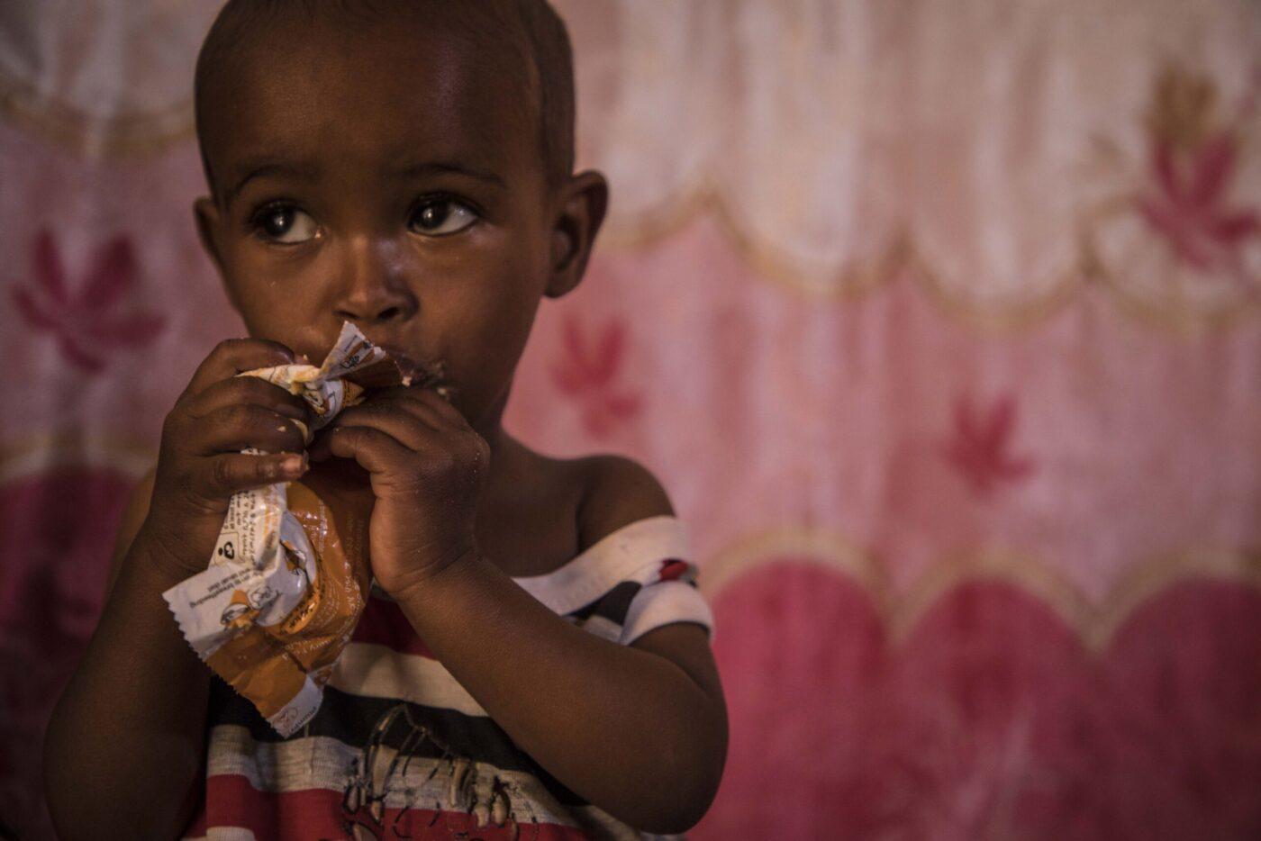 little boy eating nutrition bar